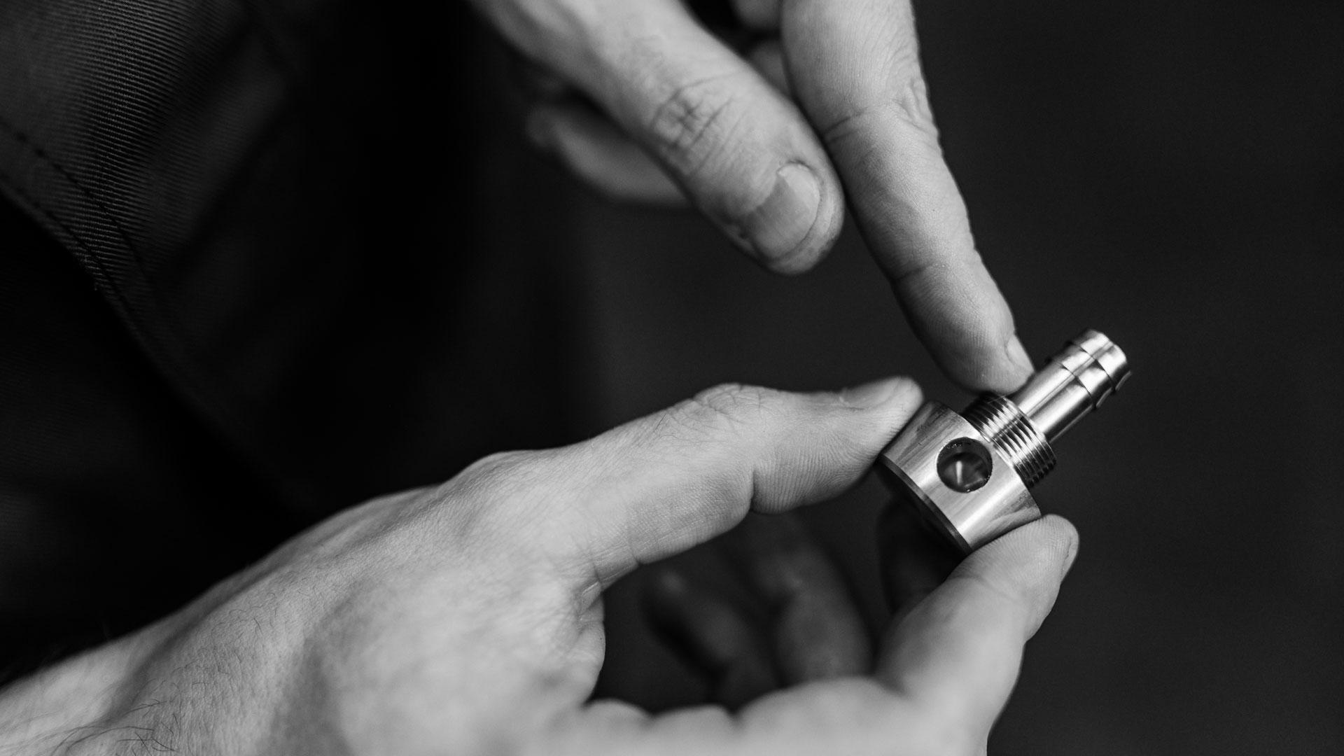 Einblick in die Produktionsstätte / Hände mit Schraube (Detailaufnahme)